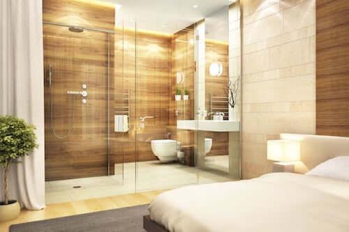 Bagno in camera con parete divisoria in vetro.