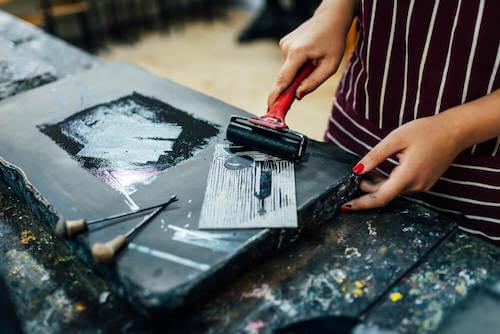 Donna che dipinge una tavola di legno.
