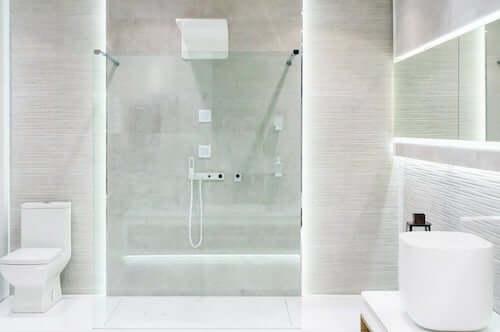 Bagno bianco minimalista con doccia aperta.