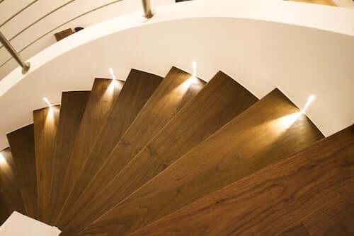 Luci a livello del suolo per illuminare gli scalini di una scala in legno.