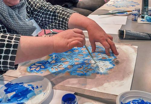 Persona che decora utilizzando la tecnica dello stencil.