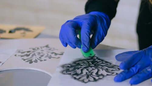 Persona che pittura un motivo decorativo stencil utilizzando una spugna.