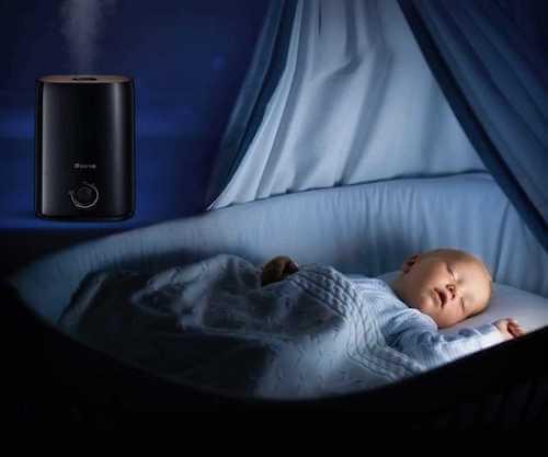 Neonato che dorme in una culla in una stanza dove c'è un umidificatore acceso.