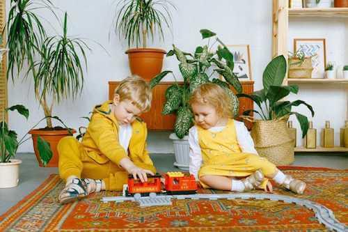Bambini che giocano in una stanza decorata con le piante.