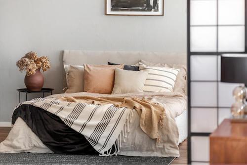 Cuscini dai colori tenui per decorare il letto.