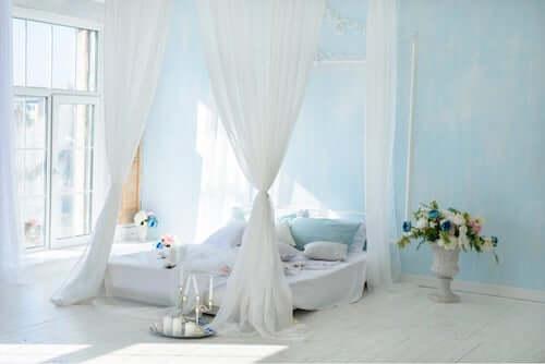 Letto a baldacchino in una camera da letto con pareti azzurro cielo.