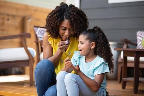 Madre e figlia che odorano una boccetta contenete un olio essenziale.
