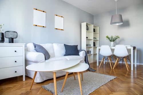 Soggiorno con divano e mobili bianchi.
