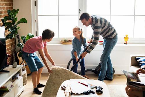 Padre e figli che puliscono il soggiorno. Padre e figli che passano l'aspirapolvere in soggiorno.