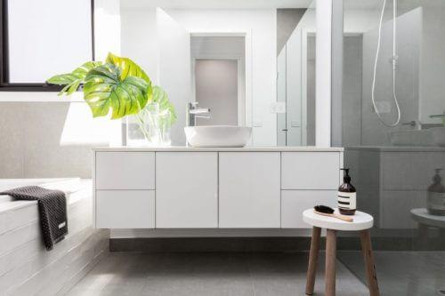 witte badkamer met een philondendron