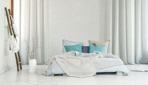 Een wit bed op de vloer met turquoise accessoires