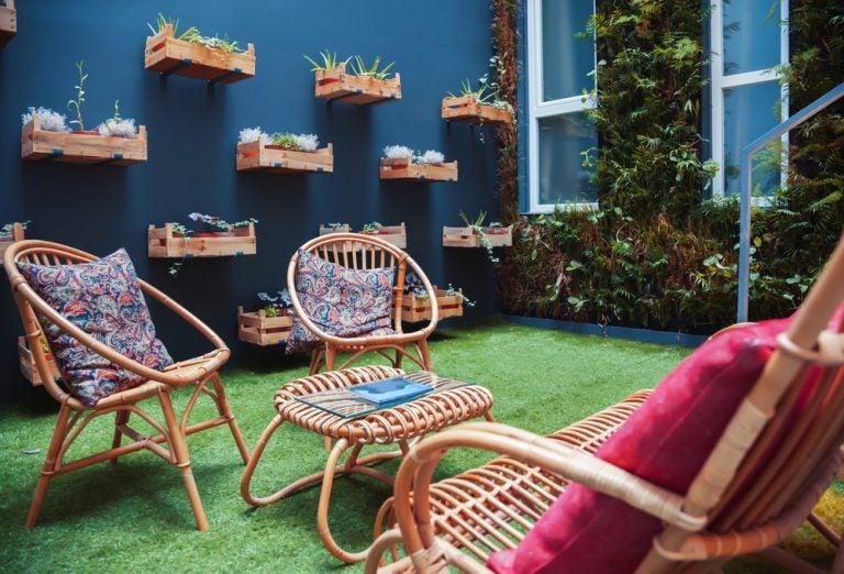 Een patio met blauwe muur en vertikale tuin