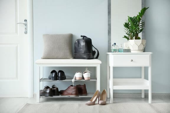 Een schoenenrek en bankje in de foyer