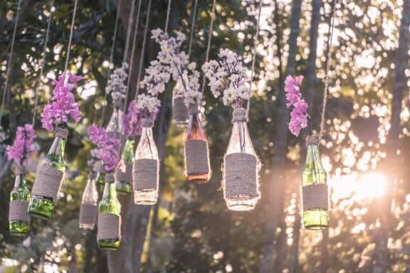 Flessen met bloemen hangen aan touw