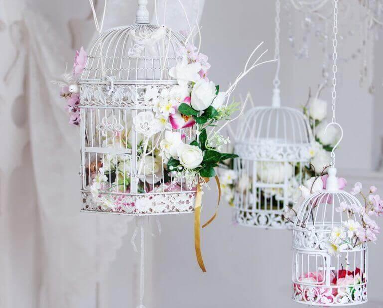Hangende witte vogelkooien met bloemen