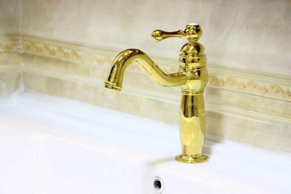 Gouden kraan voor een rustieke badkamer