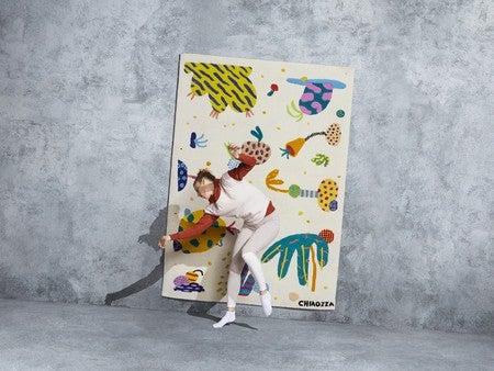 De kunstenaar Chiaozza poseert met kleed voor het ikea art event