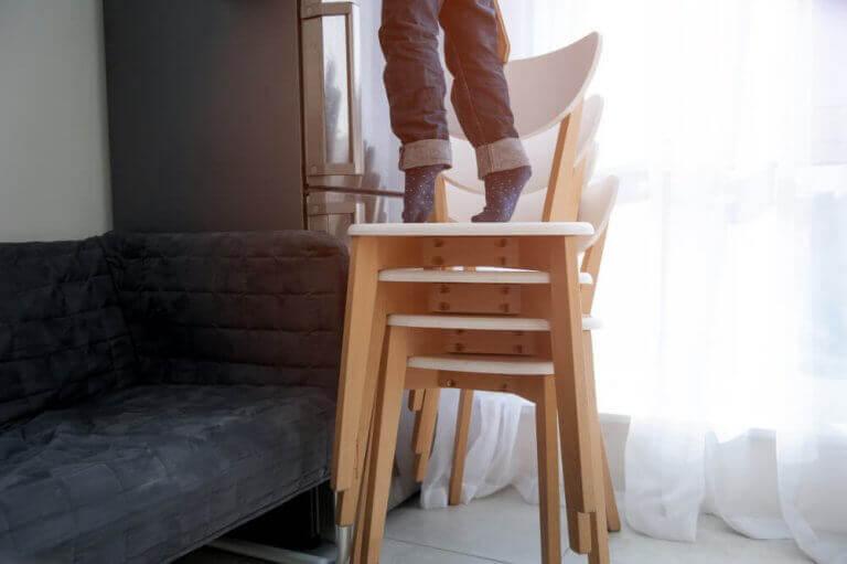 Iemand staat op opgetapelde stoelen