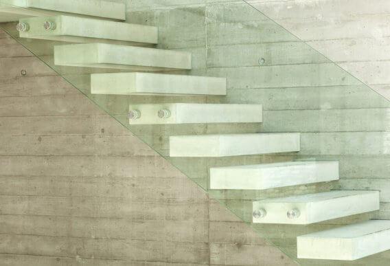 Witte betonnen trap met zijwand van glas
