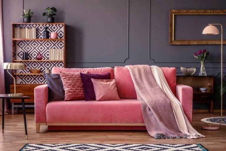 Donkergrijze muur en een roze bank