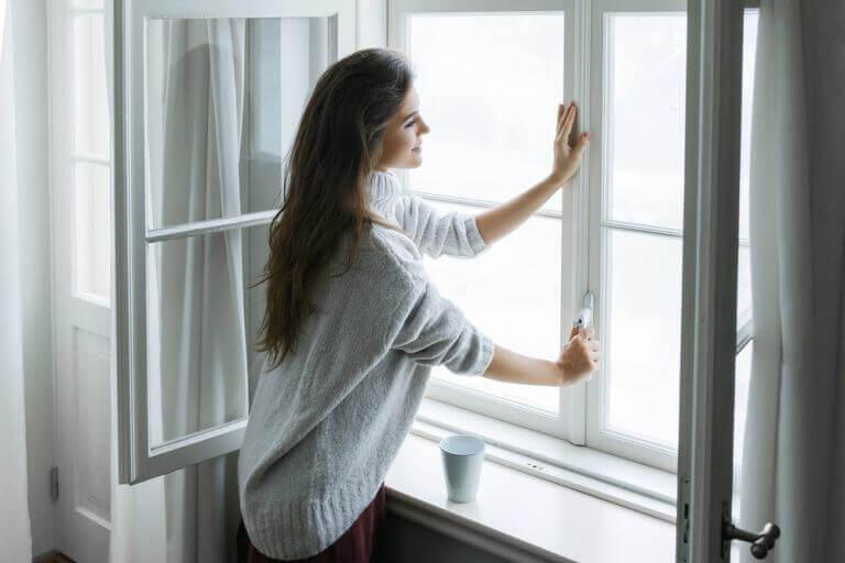 Vrouw opent gordijnen en het raam