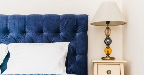 Bed met een blauw hoofdeinde en witte kussens