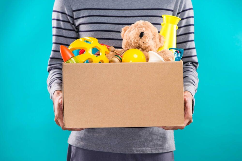 Man ruimt doos met speelgoed op