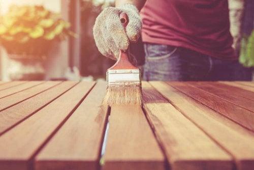 Iemand is een houten tafel aan het verven