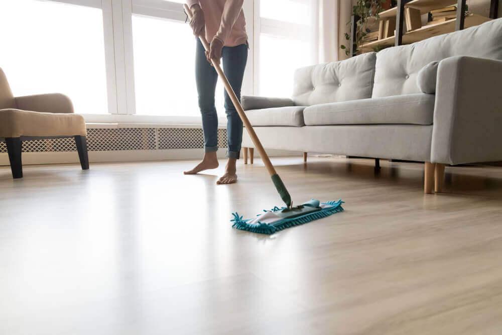 Vrouw maakt houten vloer schoon