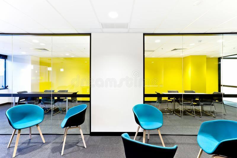 Gele muur en blauwe stoelen