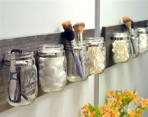 Potes de vidro como recipientes para manter as coisas no banheiro em ordem