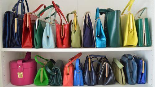 bir rafa dizili renkli el çantaları