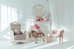 Pembe çiçeklerle dolu şömineli beyaz oda