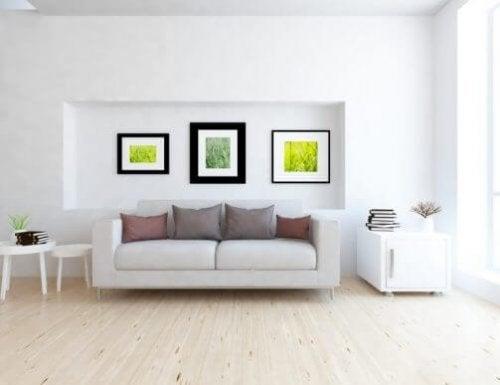 Beyaz duvarda nişin içine kontrast asılmış siyah üçlü çerçeveler ve önlerinde kanepe