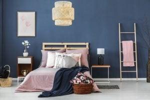 Petrol rengi duvarın önünde pembe tonlarında bir yatak