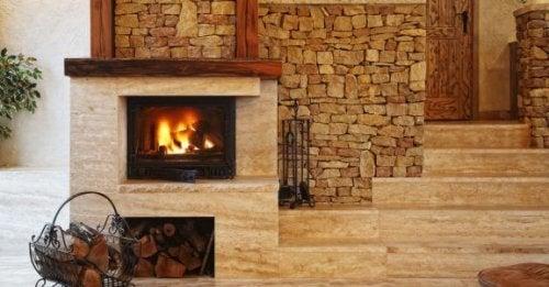 Yığma taştan duvarın önünde taştan yapılmış, yanan şömine ve önündeki odunlar