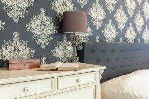 Mavi duvar kağıtlı yatak odasındaki beyaz şifoniyer