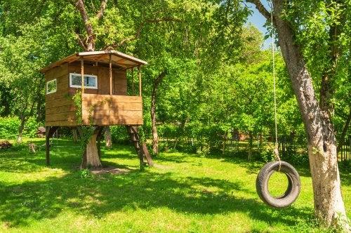 Yeşillikler içinde ahşaptan yapılmış ağaç ev ve lastik salıncak.