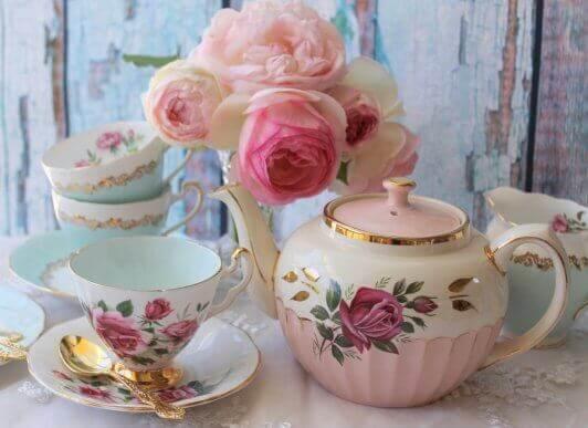 Pembe, çiçekli porselen çay takımı ve pembe çiçekler