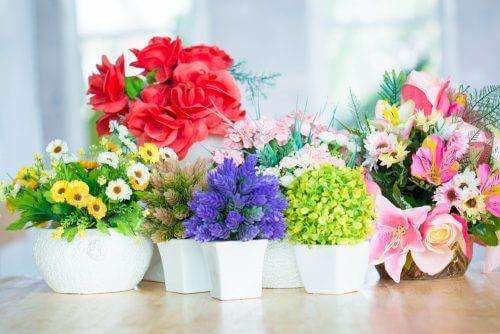 Beyaz saksılara ekilmiş farklı renk ve türde yapay çiçekler.