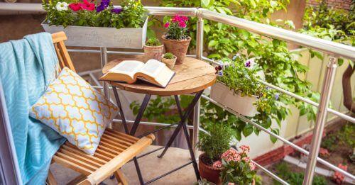 Balkonda ahşap yuvarlak masa kitap ve saksıda çiçekler, yanında ahşap sandalye