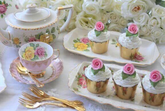 Porselen çay takımı, altın rengi servis ve kap kekler.