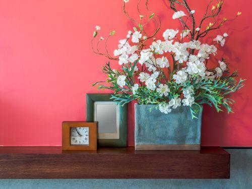 Narçiçeği rengi duvar önünde yapay çiçekler ve çerçeveler