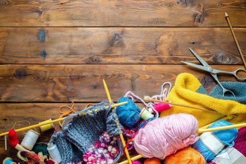 ahşap bir masa üzerinde şişler ve renkli örgü iplikleri