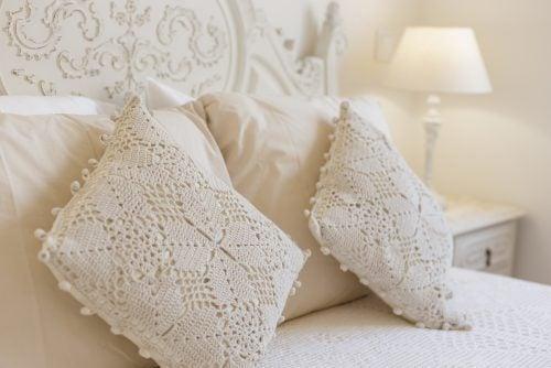 beyaz yatak örtüsü üzerinde tığ işi yastıklar