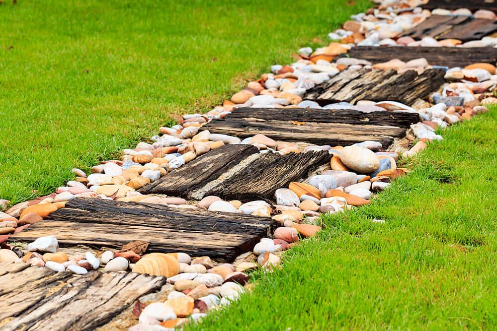 Çimenlerin ortasında taşlarla süslenmiş tahtadan patika