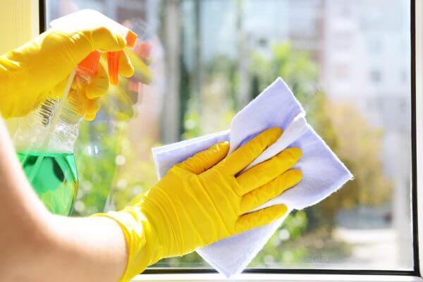 Sarı temizlik eldiveniyle cam silen kadın