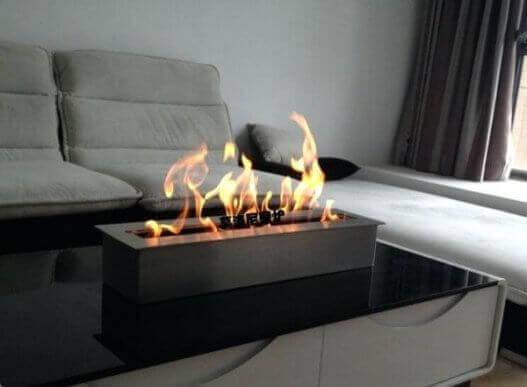 Orta sehpası üzerinde biyoethanol şömine hem bir dekoratif öğe hem de ısı kaynağı.