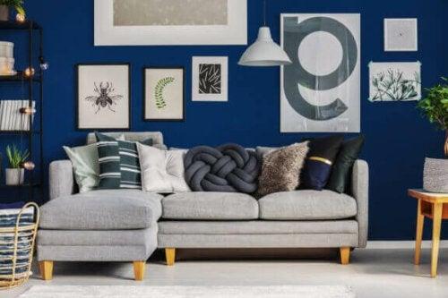 deniz mavisi duvar üzerinde beyaz gri tablolar ve bir L koltuk