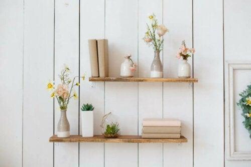 Beyaz duvarda üstünde çiçek ve kitap olan raf